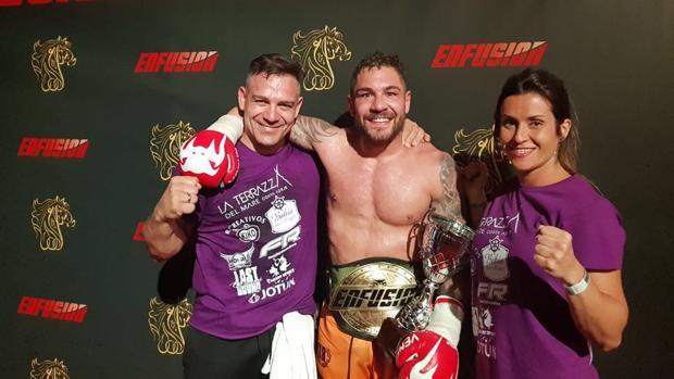 El luchador canario Jonay Risco posa con el cinturón de campéon junto a su entreandor Moisés Ruibal y Susi