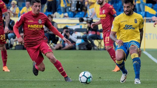 Macedo y Forlans pelean un balón durante el partido