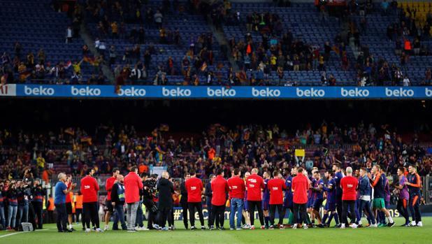 El cuerpo técnico del Barcelona hace el pasillo a los jugadores al término del clásico