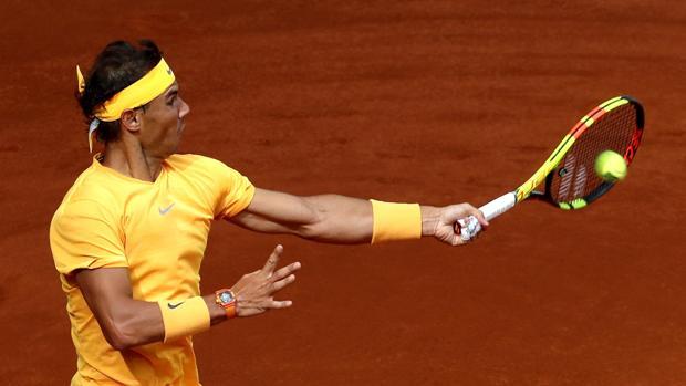 El tenista español Rafa Nadal devuelve la bola al francés Gael Monfils
