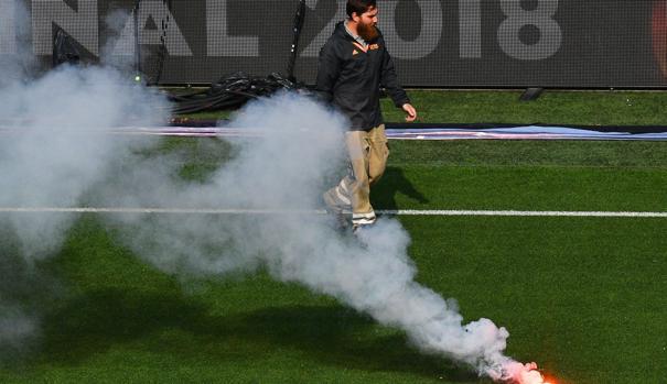 Un operario recogiendo una de las bengalas tiradas desde el exterior al estadio del Lyon