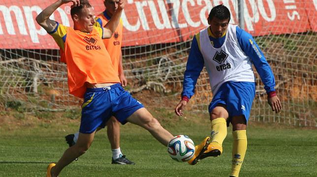 Nacho Navarrete golpea el balón en un entrenamineto ante la presión de Migue García.