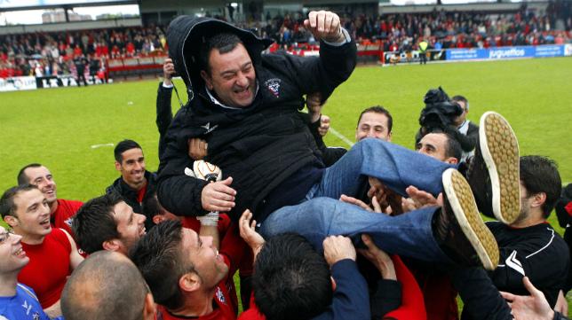 Carlos Pouso es manteado por los futbolistas del Mirandés.