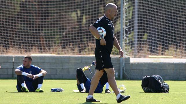 Claudio camina en un entrenamiento con sus porteros detrás.
