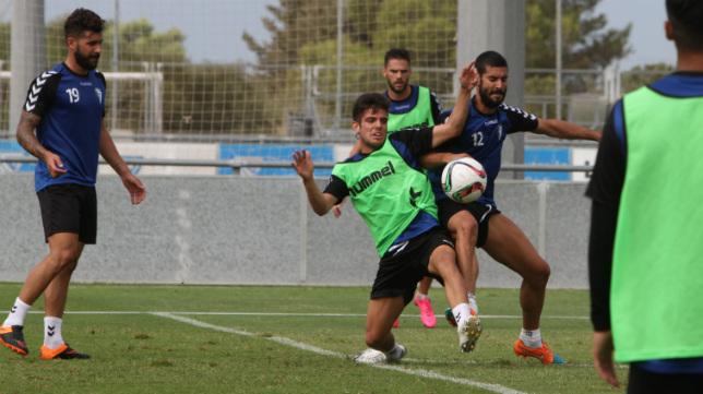 Alberto Quinatna, con el peto verde, pelea un balón en un entrenamiento.