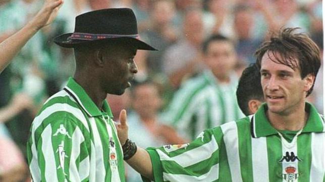 Finidi, con el famoso sombrero que recibía de la grada tras marcar un gol, recibe la felicitación de Alfonso.