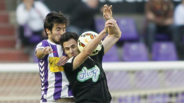 Rubén Cruz salta por el balón con un defensa del Valladolid.