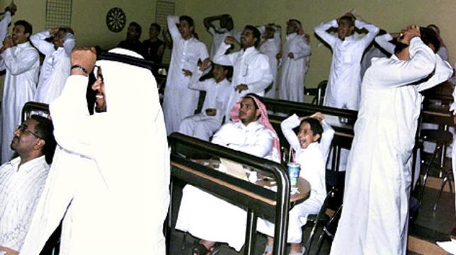 Ciudadanos de Arabiau Saudí siguen por televisión un partido de fútbol.
