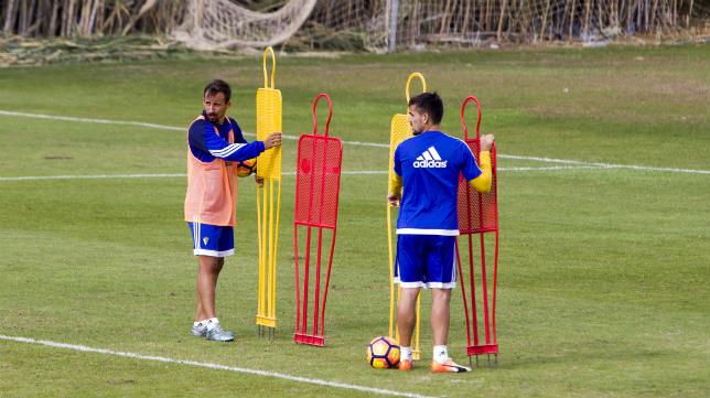 Aitor García, con peto, y Carlos Calvo colocan una barrera durante un entrenamiento.