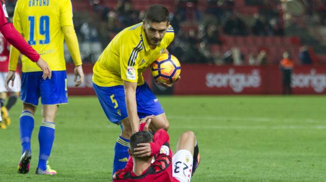 Garrido ayuda a levantarse a un jugador del Nàstic.