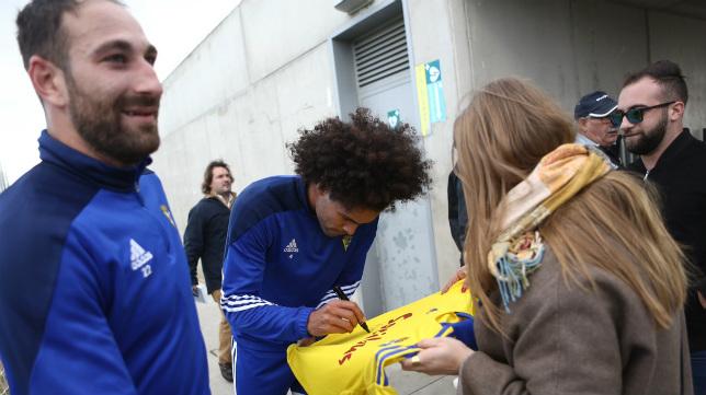 Aridane firma autógrafos a unos aficionados tras el entrenamiento de hoy.