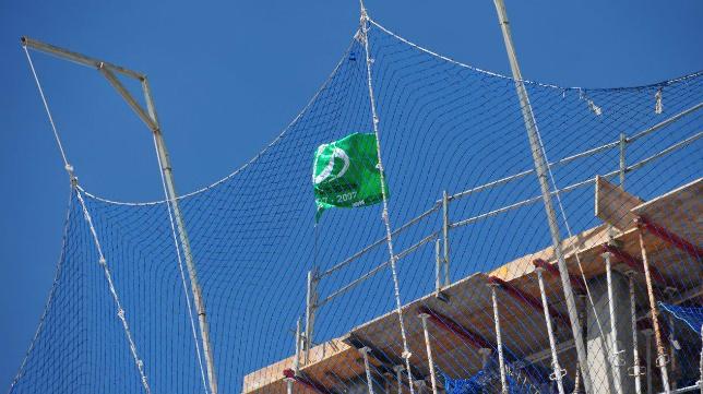 La bandera del Betis, en los nuevos edificios levantados en el antiguo solar de las bodegas Abarzuza.