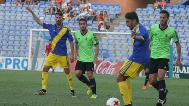 Javier Carpio juega el balón ante la presión de un rival y la mirada atenta de José Mari. :: ccf