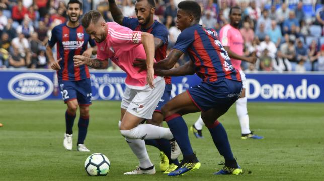 Carrillo conduce el balón perseguido por tres rivales del Huesca.