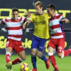 Álex Fernández conduce el balón ante dos rivales del Granada.