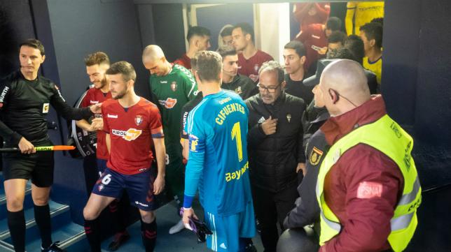 Jugadores de Osasuna y Cádiz se preparan para salir al césped de El Sadar en el partido de ida.