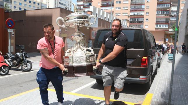 Dos empleados del Cádiz CF cargan con el Trofeo Carranza.