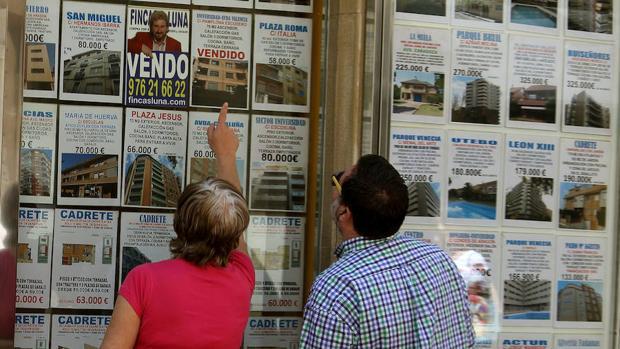 Dos personas buscando piso en una inmobiliaria de Zaragoza