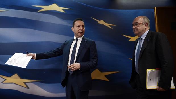 Yannis Stournaras (izq.) junto a Joaquín Almunia (der.) en la sede de la CE en 2014, cuando ocupaba el cargo de ministro de Finanzas griego