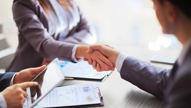 Un jefe y un empleado estrechándose la mano