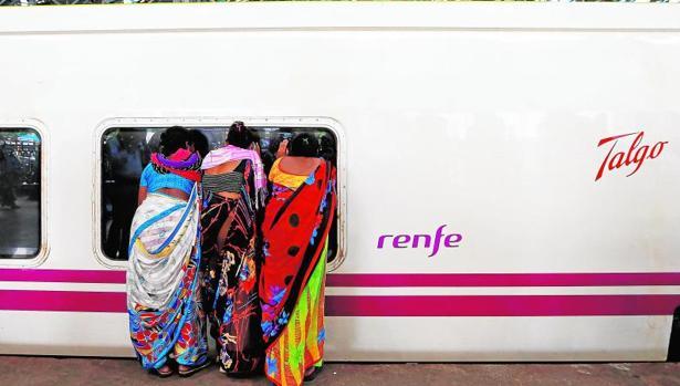 Tres mujeres indias observan el interior del vagón de un tren Talgo que cubre servicio en aquel país