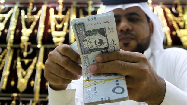 Un comerciante saudí cuenta dinero en una tienda en Riad
