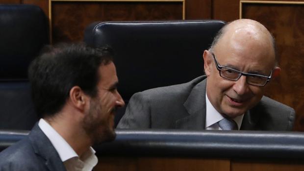 El ministro de Hacienda en funciones, Cristóbal Montoro, conversa con el diputado de Unidos Podemos Alberto Garzón (i), al inicio del pleno que se celebra esta tarde en el Congreso de los Diputados