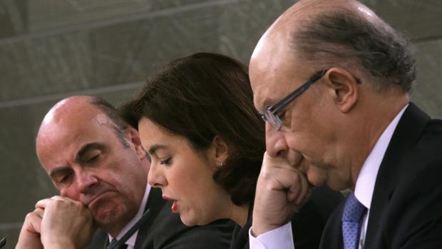 El ministro de Economía, Luis de Guindos, la vicepresidenta del Gobierno, Soraya Sáenz de Santamaría, y el ministro de Hacienda, Cristóbal Montoro