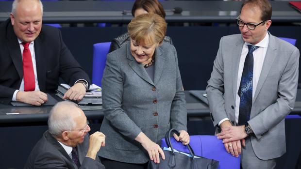 La canciller alemana, Angela Merkel (c), conversa con su ministro de Finanzas, Wolfgang Schäuble (i); y de Transporte, Alexander Dobrindt