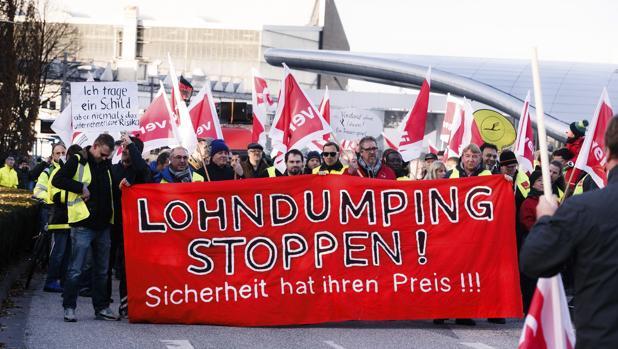 Empleados de la aerolínea alemana Lufthansa sostienen una pancarta en la que se puede leer '¡Parad la liquidación de los salarios! la seguridad tiene su precio' durante una manifestación