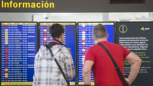 Dos viajeros observan el panel de salidas en el aeropuerto de El Prat (Barcelona)