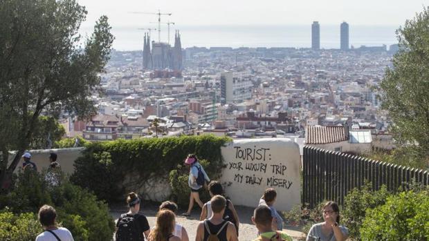 Un grupo de turistas pasea por los alrededores del Parque Guell de Barcelona , donde últimamente han aparecido pintadas contrarias al turismo masificado