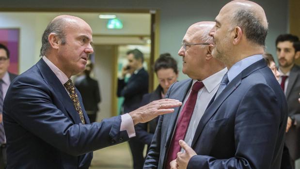 El ministro español de Economía, Luis de Guindos conversa con el ministro de Finanzas de Francia, Michel Sapin y el comisario europeo de Asuntos Económicos y Financieros, Pierre Moscovici, en un Eurogrupo el pasado mes de merzo