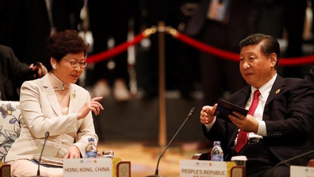 El presidente chino, Xi Jinping (dcha), conversa con la jefa ejecutiva de Hong Kong, Carrie Lam, mientras asisten a la cumbre de diálogo APEC-ASEAN