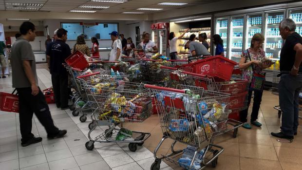 Venezolanos buscan alimentos en los pasillos de un supermercado