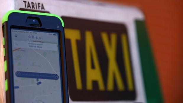Un teléfono con la aplicación de Uber frente a un taxi
