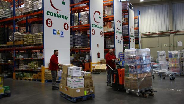 Trabajadores mueven palets en un almacén de la cadena granadina Covirán