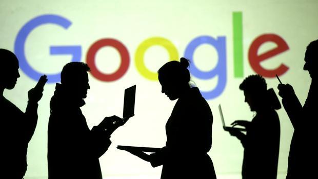 Un grupo de personas utilizando ordenadores y móviles delante de una pantalla de Google