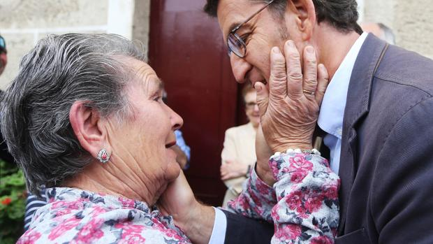 Una vecina de Os Peares (Orense) pueblo natal de Feijóo, saluda cariñosa al candidato del PP a la Xunta de Galicia