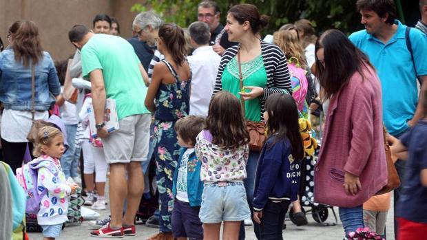 Una madre acompaña a su hijos a las puertas del colegio, en el inicio de una jornada lectiva