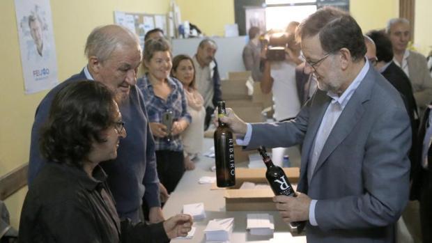 El presidente del Gobierno, Mariano Rajoy, recibe como regalo dos botellas de Ribeiro, en la sede local del PP