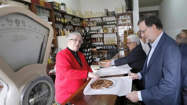 Rajoy recibe una tarta que le regala la dueña de una tienda en agradecimiento por su visita