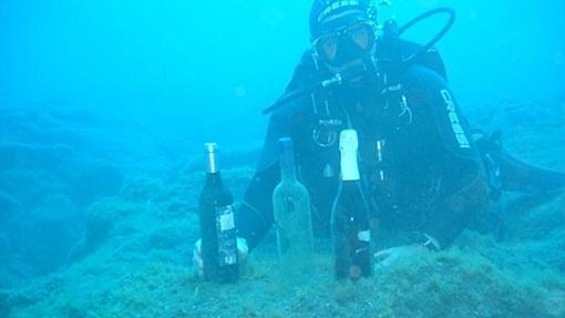 Un buceador muestra varias botellas «submarinas» de la Bodega Castro y Magán, en La Palma