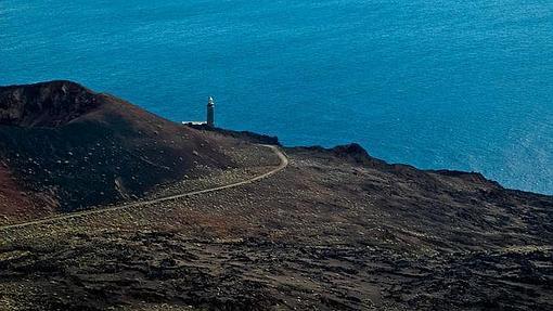 La arena volcánica de El Hierro desemboca en el mar con el faro de Orchilla como testigo