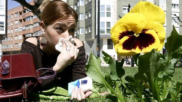 Una chica estornuda por consecuencia de las alergias