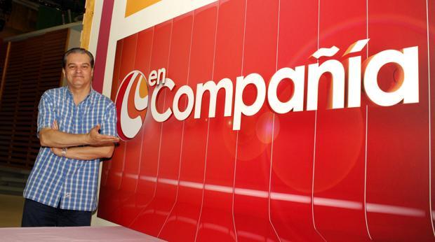 El presentador, Ramón García, posa junto al cartel del programa de televisión
