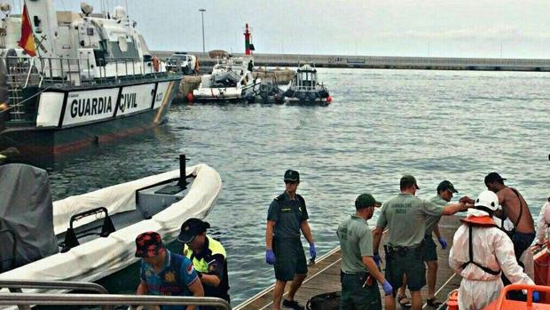 Efectivos de la Guardia Civil con los rescatados en el puerto de Alicante.