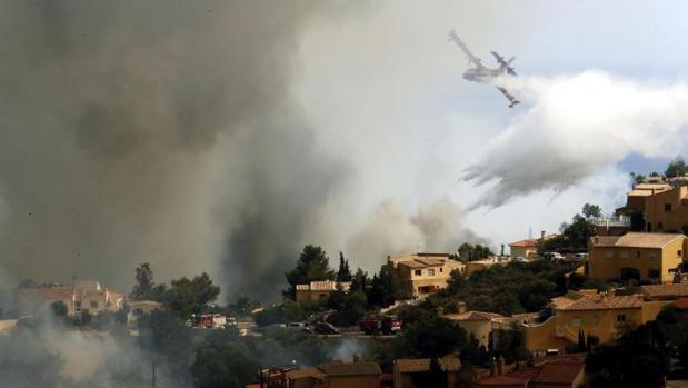Un hidroavión intentan apagar las llamas en la urbanización Cumbres del Sol junto al paraje natural de La Granadella