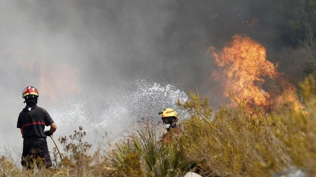 Efectivos de bomberos intentan apagar las llamas en la urbanización Cumbres del Sol junto al paraje natural de La Granadella
