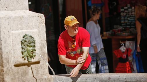 Un hombre se refresca en una fuente en Valencia